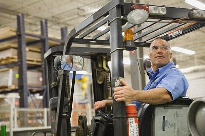 Worker driving forklift in factory